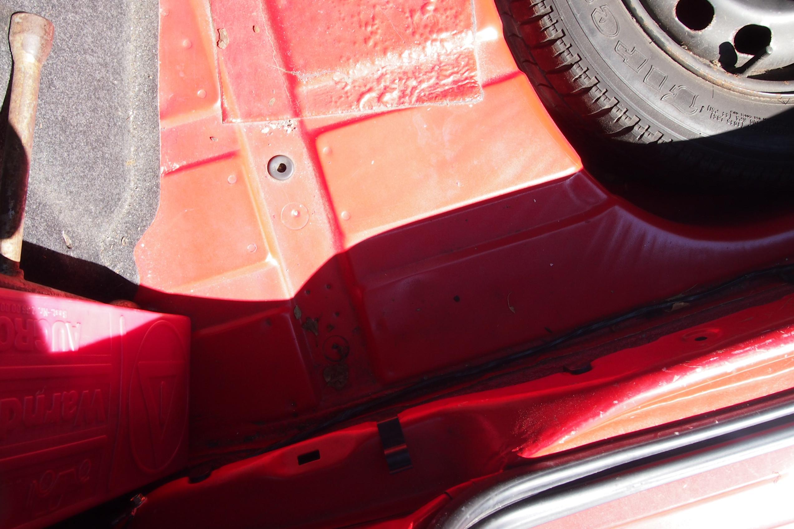 Kofferraumboden unter dem Teppich eines roten Ford Escort